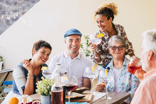 Family and friends at lunch all together at home in the terrace - eating and drinking food and beverages - smile and having fun- friendship with mixed ages senior and middle age people