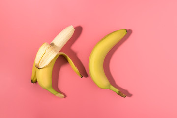 Two bananas on pink background with contrast shadows, flat lay