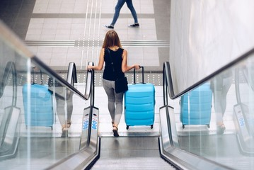Woman with blue baggage suitcase on escalator