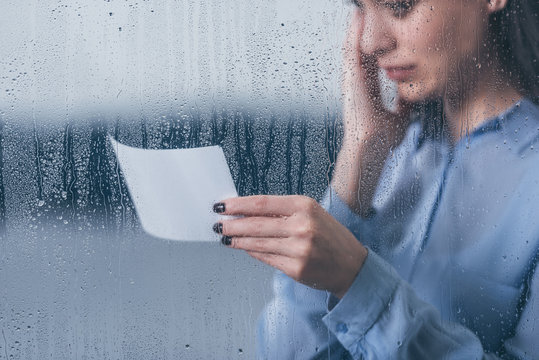 cropped view of grieving woman holding photograph and crying through window with raindrops