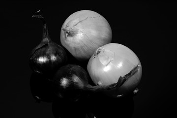 onions and blue onions are reflected on a black mirror table