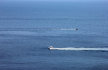 best blue sea in full screen and small ripples on the water and two motor boats cross the water surface