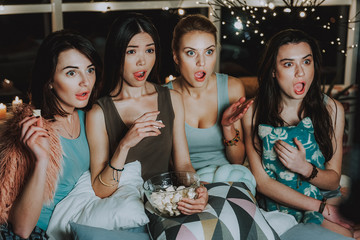 Surprising girls company eating marshmallow and watching movie