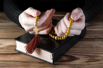 Woman praying and holding rosary beads over table with Holy Bible. Religion concept. Close up.