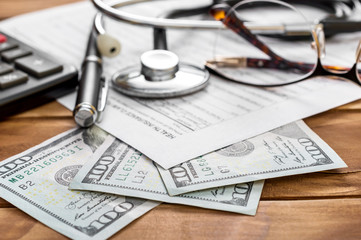 Health insurance claim form with money, calculator and stethoscope on the table.