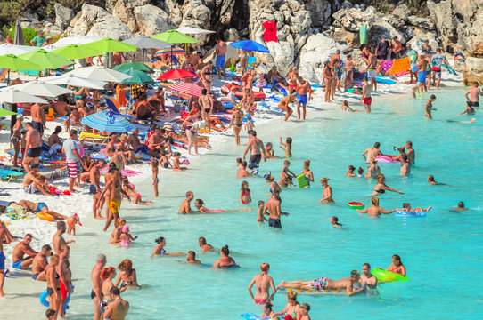Large crowd of people on the beach sunbathing and enjoyng vacation by the sea. People have motion blurr applied.