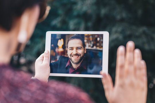 Young woman holding a tablet in her hands, having a video call chat with her freelancer boyfriend who is away on business trip. Concept of keeping long distant relationship in career oriented world.