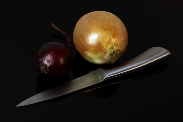 onions, blue onions and a sharp knife are reflected on a black mirror table
