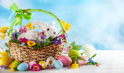 Easter composition with bunny in basket, spring flowers and colorful Easter eggs .