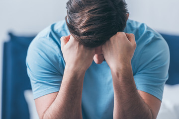 selective focus of grieving man covering face with hands and crying at home