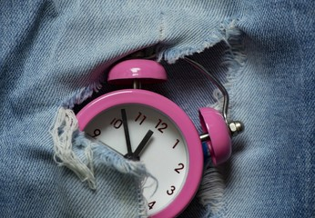 a small pink alarm clock breaks through a hole in denim