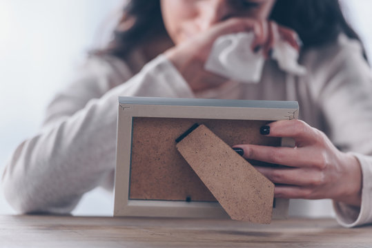 cropped view of upset woman holding picture frame and crying at home