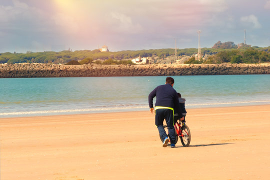 Father teaches his son to ride a bike on the beach.