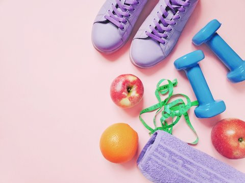 Flat lay photo gym women's items. Purple sneakers, apple fruits, orange, dumbbells, measuring tape and cotton towel. Fitness, sport, healthy lifestyle concept