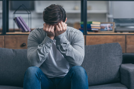 man sitting on couch, crying and and covering face with hands at home