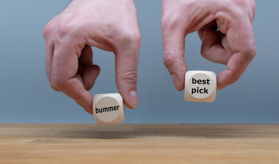 """Symbol for a good decision. Two Hands hold two dice with the words """"bummer"""" and """"best pick"""". The dice with the label """"best pick"""" is chosen."""