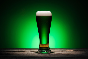glass of ale standing on wooden table on st patricks day on green background