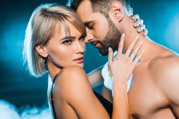 sensual girlfriend embracing shirtless boyfriend on blue smoky background