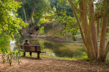 Woman sitting on a bench near lake background.