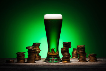 glass of irish ale standing on wooden table near golden coins on green background