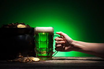 cropped view of man toasting glass of irish beer with pot of gold on green background