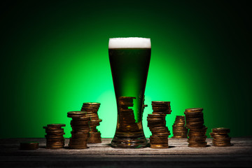 glass of ale standing on wooden table near golden coins on green background