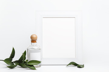 Wooden frame in the composition of glass bottles and fresh green leaves on a white table. The concept of spa treatments and body care. Mockup.