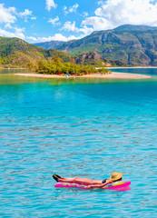 Girls in bikini lying on air bed in the turqouise sea - Oludeniz Beach And Blue Lagoon, Best beaches in Fethiye, Turkey