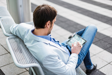 Businessman sitting on a bench, using digital tablet