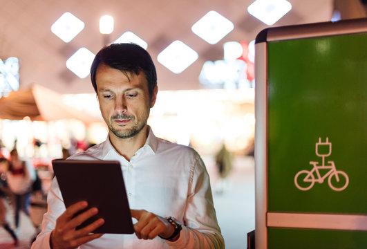 Businessman using digital tablet next to charging station