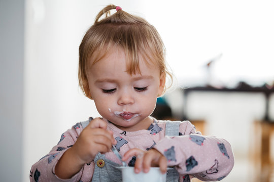 Portrait of baby girl eating yogurt at home