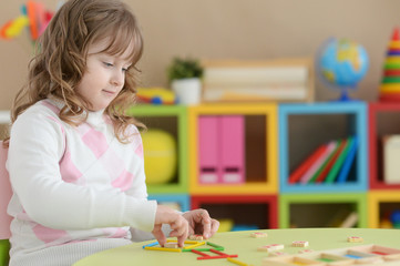Portrait of cute curly girl learning to count with sticks at room