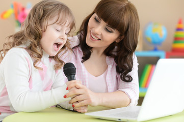 Cute little girl with young mother singing karaoke with laptop at home