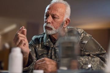 Pensive military veteran taking medicine.