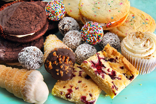 Assortment of baked sweet treats, including chocolate rum balls, vanilla cookies, raspberry squares and a cupcake with maple icing.