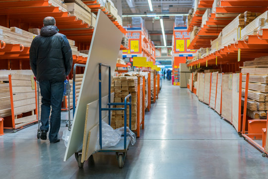 A man in a hardware store. Carts loaded with boards. shop of building materials. Racks with boards, wood and building material. loaded cart in a hardware store
