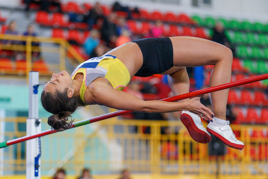 Professional female athlete jumping over bar