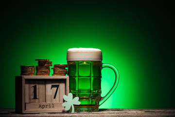 glass of green irish ale near golden coins and cube calendar on green background