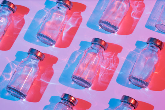 Glass bottle for vaccination with color lighting. Conceptual photo about the danger of viral diseases.