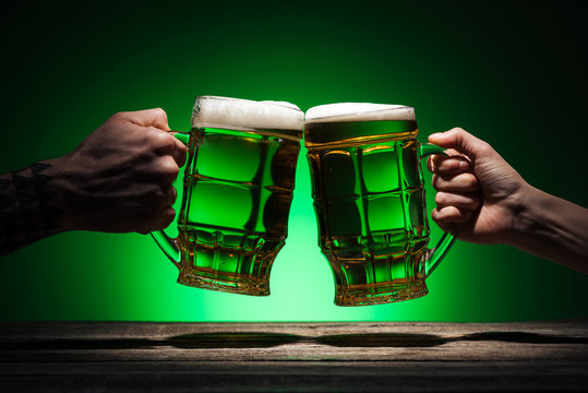 cropped view of friends toasting with glasses of beer on st patricks day on green background