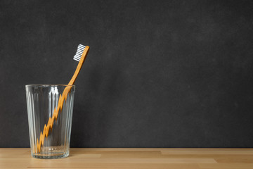 a wooden toothbrush in a glass on black background