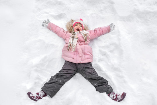 A happy little toothless girl in the winter walk, in the nature. A child making an angel on the snow.