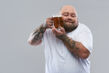 Waist up of bearded tattooed man pressing glass of beer to his cheek