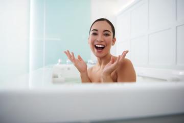 Happy smiling asian lady having fun in bath