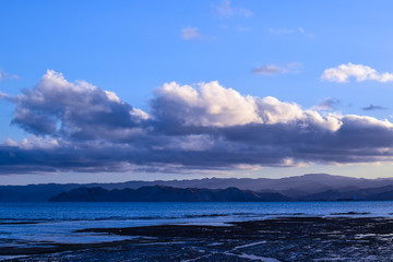 The blue sky and sea are only seperated by dark land and light clouds in Gisborne, new Zealand.