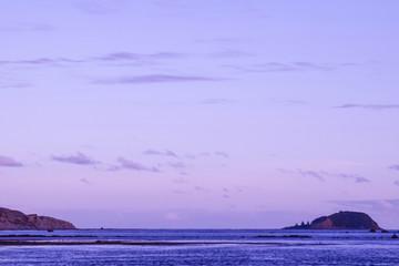 The still sea before an empty beach under a brilliant blue sky in Gisborne, New Zealand.