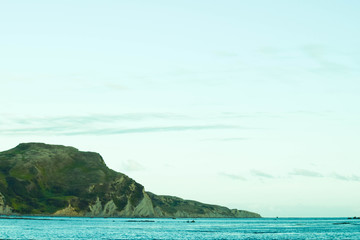 The green hill stands tall over the blue waves below in Gisborne, new Zealand.