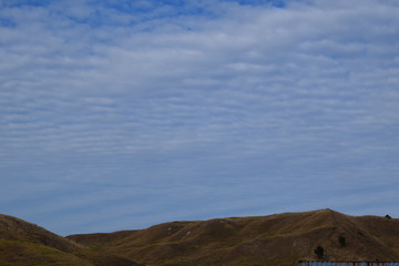 The long hill range holds up the patterned blue sky in Gisborne, New Zealand.