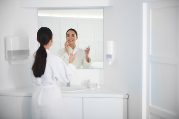 Smiling asian lady apply face cream before mirror