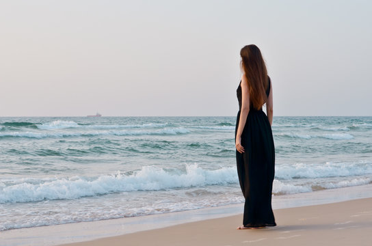 Young brunette woman in black dress standing on beach and looking to the sea.